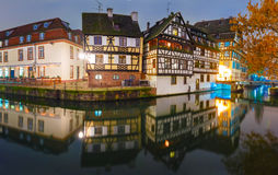 Night Petite France in Strasbourg, Alsace. Panorama of traditional Alsatian half-timbered houses with mirror reflections in Petite France during twilight blue Stock Photos