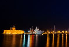 Night photo of ancient fortress and pier in Rhodes city on Rhodes island, Dodecanese, Greece. Stone walls and bright night lights stock photography
