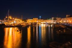 Night photo of ancient fortress and pier in Rhodes city on Rhodes island, Dodecanese, Greece. Stone walls and bright night lights royalty free stock image