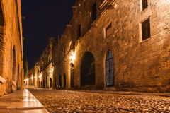 Night photo of ancient street of the Knights in Rhodes city on Rhodes island, Dodecanese, Greece. Stone walls and bright night royalty free stock photography