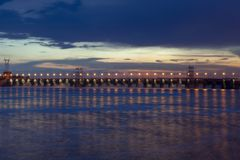 Night photo of the dam, sross water, clouds at sunset, leaden water surface stock image