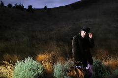Night photo of man walking. Colorful night portrait of man with bag and hat walking Stock Photo