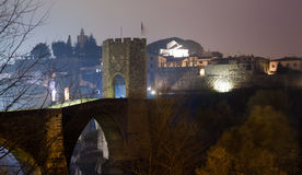 Night photo of Medieval bridge with city gate. Besalu, Catalonia. Night illumination of old town with medieval bridge at Besalu. Catalonia, Spain royalty free stock images
