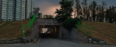 Night Photo of Underpass. Night photo of an underpass with apartments, trees and a gray overcast sky in the background Stock Photo