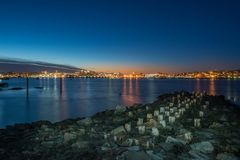 Night photo view of Portland Maine, USA. The smooth water, the city`s buildings on the other shore are reflected in the water of the bay Royalty Free Stock Images