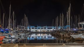 NIGHT PHOTOGRAPH OF A PORT OF BOATS AND A PUB BAR royalty free stock image