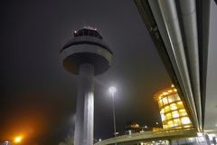Night photograph of the tower of an airport with poor lighting and the parking garage for the passengers in the background. stock image