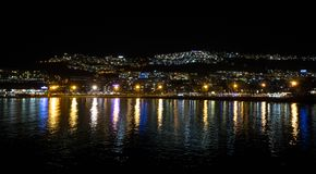 Night photography of the city with blue and yellow lights reflecting in the ocean. Puerto Rico, Gran Canaria, Spain. Royalty Free Stock Photos