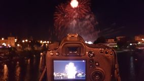 Night photography. Photo camera doing night-time photography of the fireworks of the Seville fair in Andalusia, Spain. Photograph taken from the bridge of San Stock Photography