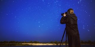 Night photography. Silhouette of photographer on background of starry sky. Long exposure. Stars at night. Starry landscape