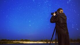 Night photography. Silhouette of photographer with camera on tripod on background of starry sky. Many stars in night sky. Dark