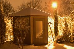 Night Picture of the rounded garden house in the winter time covered by snow and lighted by street lamp with orange light. Royalty Free Stock Photo