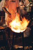 Street food chef cooking meat and fish in a pan with fire and flames under it. Chinatown, Bangkok, Thailand. Night picture of a street food chef cooking meat and royalty free stock photography