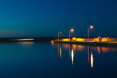 Night pier. A pier at night with city lights reflecting in calm water Stock Photography