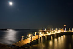 Night pier. With lights, moon reflection on the water Royalty Free Stock Images