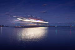 Night in the port. Ferry enters the harbor, sunset over the sea stock images