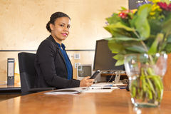Night porter behind the front desk. Young secruity guard manning the front desk of a large company during the night shift, with a computer monitor and cctv Stock Photography