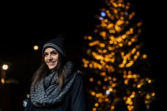 Night portrait of a beautiful brunette woman smiling enjoying winter in park.Winter joy.Winter holidays.Positive emotions. royalty free stock photography