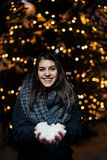 Night portrait of a beautiful brunette woman smiling enjoying winter in park.Winter joy.Winter holidays.Positive emotions. stock photo