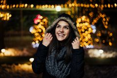Night portrait of a beautiful happy woman smiling enjoying winter and snow outdoors.Winter joy.Winter holidays.Positive emotions. stock photography