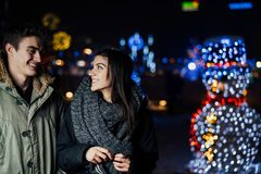 Night portrait of a happy couple smiling enjoying winter and snow aoutdoors.Winter joy.Positive emotions.Happiness stock photography
