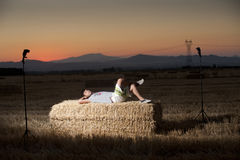 Night portrait of a young man. On top of a straw bale Royalty Free Stock Images