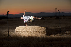 Night portrait of a young man. Who jump out of a top of a straw bale Stock Photos