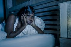 Night portrait of young sad and worried black african American woman in bed at home sleepless and stressed feeling depressed suffe. Lifestyle night portrait of stock photography