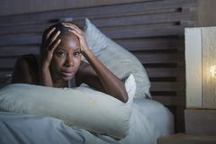 Night portrait of young scared and stressed black african American woman on bed upset unable to sleep suffering hangover headache. Lifestyle night portrait of royalty free stock images