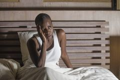 Night portrait of young scared and stressed black afro American woman on bed upset unable to sleep suffering hangover headache and. Lifestyle night portrait of stock image