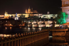 Night Prague gothic Castle and St. Nicholas' Cathedral with Charles Bridge, Czech Republic Stock Photo