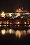 Night Prague gothic Castle and St. Nicholas' Cathedral with Charles Bridge, Czech Republic Royalty Free Stock Photos