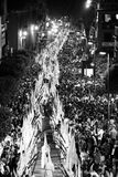 Night procession through Seville by penitents. Night procession through Seville by religious penitents in robes and conical hats during the easter Holy Week in Stock Photo