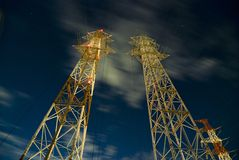 Night pylons. High-rise industrial electricity pylons over starry night sky Royalty Free Stock Photos