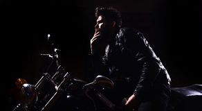 Night racer concept. Man with beard, biker in leather jacket sitting on motor bike in darkness, black background. Macho. Brutal biker in leather jacket riding Royalty Free Stock Photo
