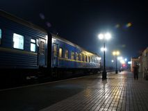 Night Rail-Road Station. Empty rail road station in the night, only one lonely person is standing on platform. Blue train's wagons is standing on the left side stock image