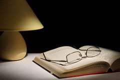 Night reading. Reading glasses resting on top of open book next to night lamp Stock Photos