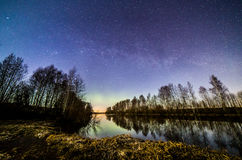Night by the river. Beautiful spring night and starlit sky by the river. Fascinating colors appeared in the sky. Also mild auroras were present Stock Photo