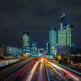 Night road with skyscrapers of La Defense, Paris, France. Night multi-lane road with skyscrapers of the La Defense, Paris, France. Long exposure Stock Photo