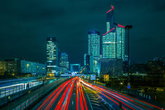 Night road with skyscrapers of La Defense, Paris. Night multi-lane road with skyscrapers of the La Defense, Paris, France. Long exposure Stock Images