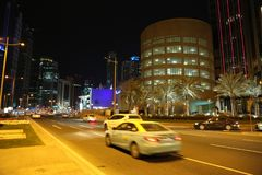 Night road traffic in financial centre in Doha, Qatar. QATAR, DOHA, MARCH 20, 2018: Night road traffic in financial centre in Doha - capital and most populous royalty free stock image