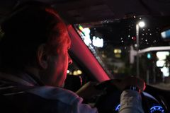 Night road. View from inside car. Natural light. the man driving a car at night in the face reflects the red color of the parking royalty free stock image