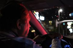 Night road. View from inside car. Natural light. the man driving a car at night in the face reflects the red color of the parking stock photos