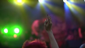 Cool night rock concert in the front row of the crowd of applause under the light of illumination. slow motion close-up