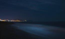 Night scape of the sea coast. Beach in darkness, city lights at horizon. Alanya, Turkey Stock Photography