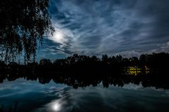 Night scary scene. Full moon above the pond with silhouette of a tree Stock Photo