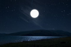 Dark night full moon. Dark night scene in mountain with full moon reflexed in lake blue water and starlit sky Stock Image