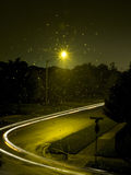 Night Scene. One streetlamp shines on a dark street while the headlights of a car whizz by Royalty Free Stock Photography
