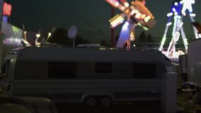 Night scene tilt-shift at dusk amusement park. Night scene of amusement park with parked trailer and Ferris wheel merry-go-round spinning in the background at stock video footage