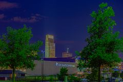 Night scene CHI health center conference center and First National Bank building. Men`s College World Series Omaha baseball logo hologram on FNBO headquarters stock photo